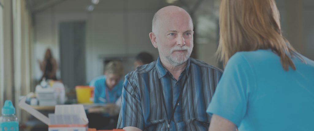 Man sitting at desk looking at woman who is talking to him