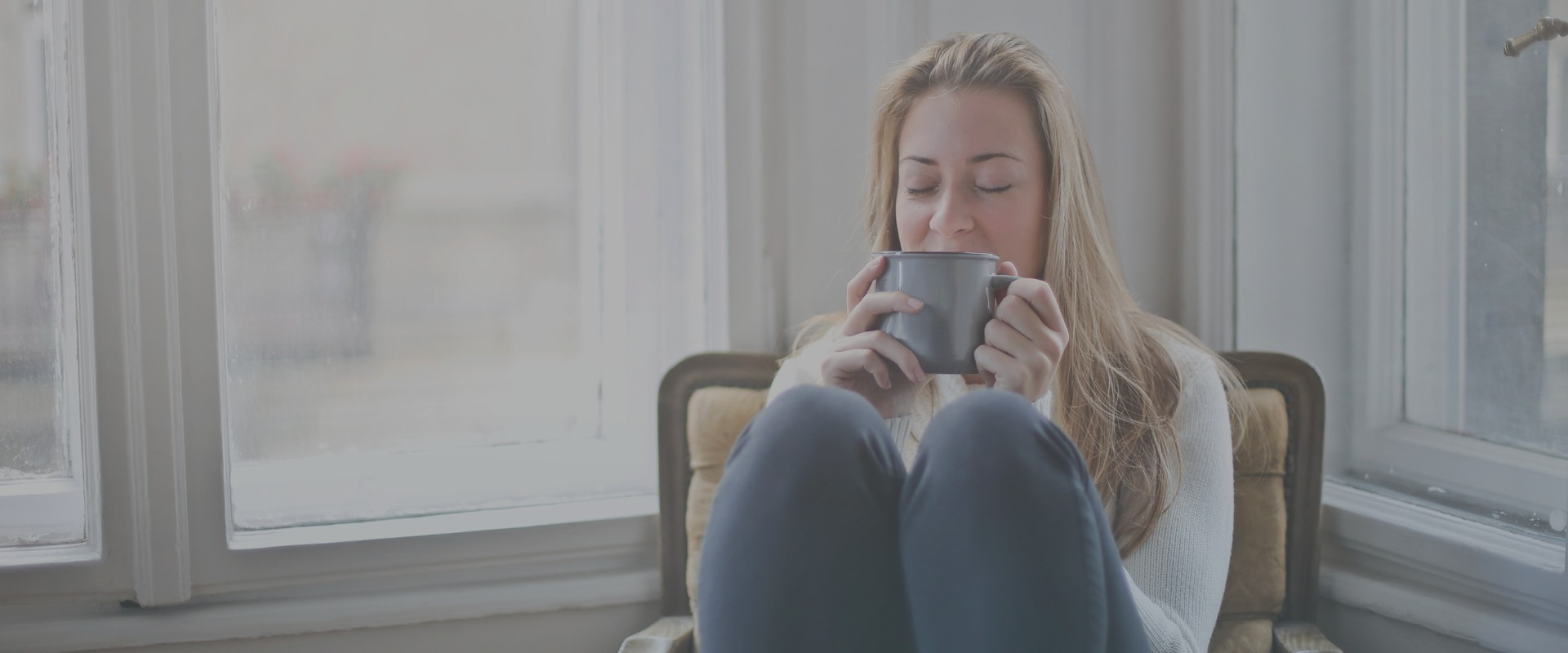 Woman sitting on chair next to window with eyes closed whilst drinking from a mug