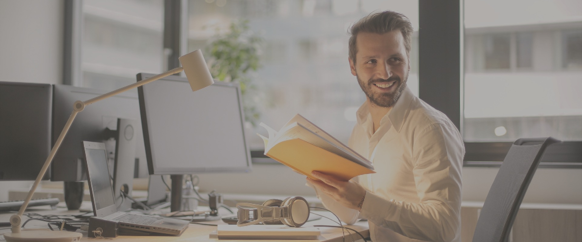 Man sitting at desk whilst smiling and holing a book