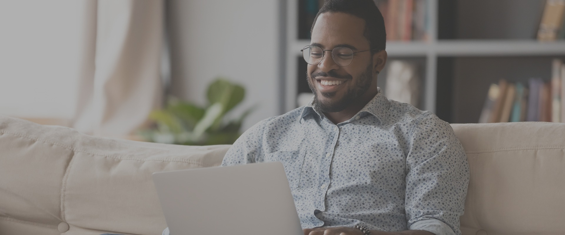 Man sitting on sofa with laptop and smiling